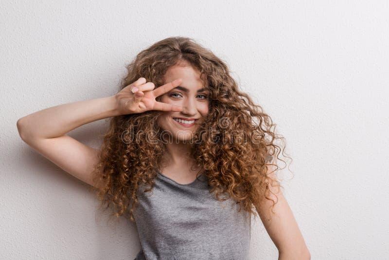 Mujer alegre hermosa joven en el estudio, fingeres que forman V foto de archivo libre de regalías