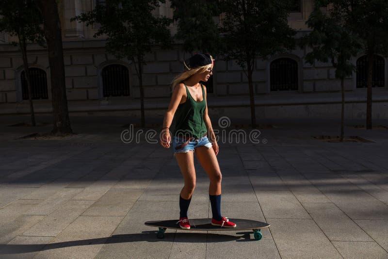 Mujer alegre joven atractiva con un monopatín imagen de archivo