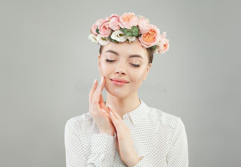 Mujer alegre joven con la piel, las flores y la manicura claras perfectas fotografía de archivo libre de regalías