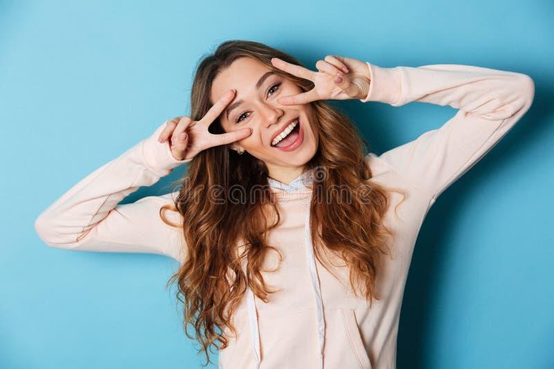 Mujer alegre joven divertida linda que muestra gesto de la paz imagen de archivo