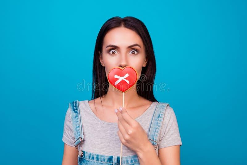 Mujer alegre joven en el fondo azul que cierra su boca con c foto de archivo libre de regalías