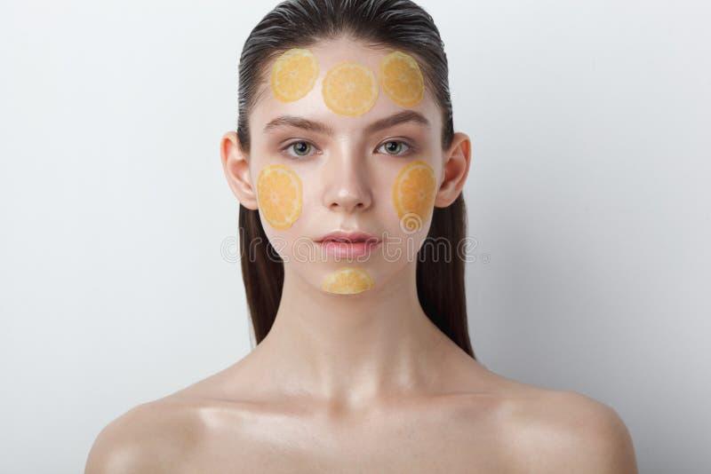 Mujer alegre joven hermosa con la máscara en su cara en el fondo blanco fotos de archivo