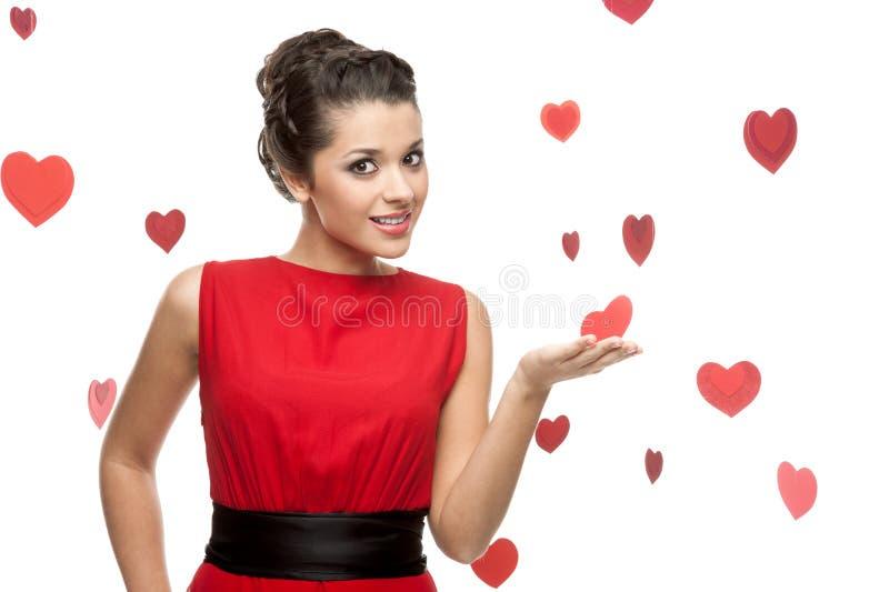 Mujer alegre joven que lleva a cabo el corazón de papel rojo imagenes de archivo