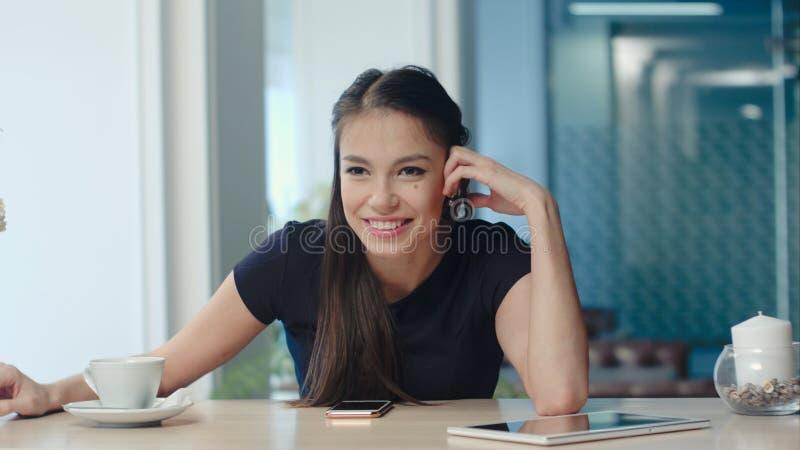 Mujer alegre joven que se sienta en un café y que habla con un amigo fotos de archivo