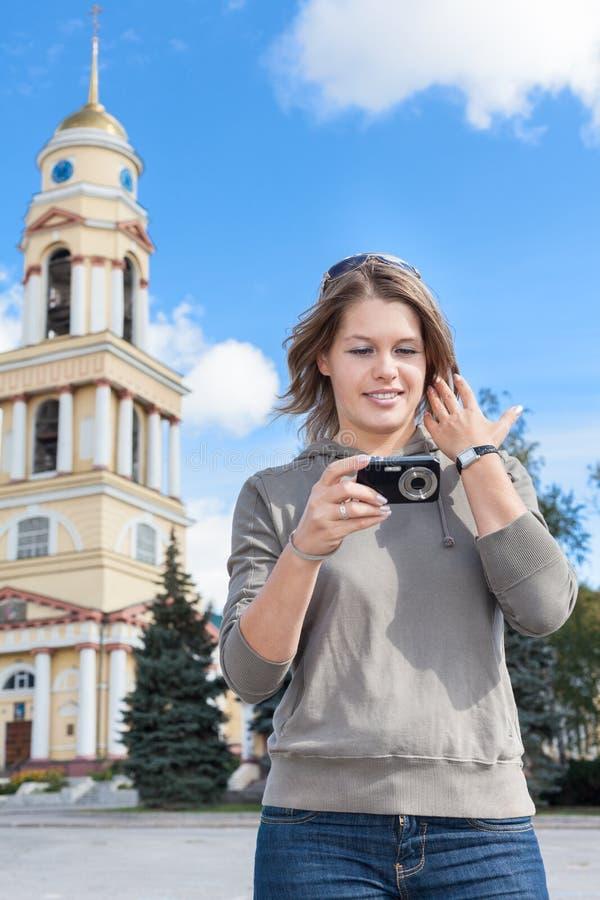 Mujer alegre joven una fotografía con la cámara fácilmente manejada, mirando la pantalla Soportes detrás del campanario de la igl foto de archivo libre de regalías