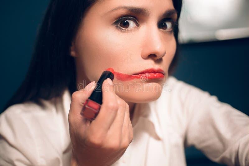 Mujer alegre loca que aplica el lápiz labial foto de archivo