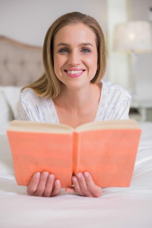 Mujer alegre natural que miente en la cama que sostiene el libro foto de archivo libre de regalías