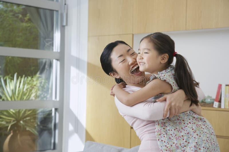 Mujer alegre que abraza a su hija foto de archivo libre de regalías