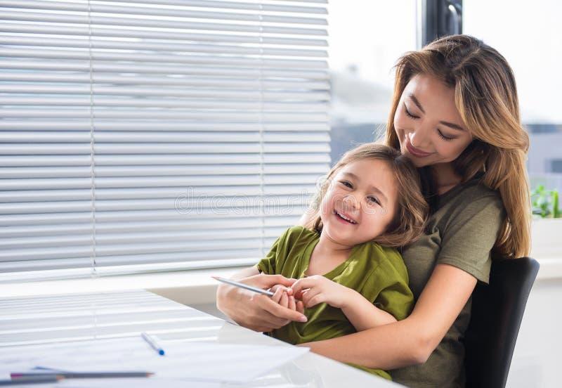 Mujer alegre que abraza a su hija con cariño imágenes de archivo libres de regalías
