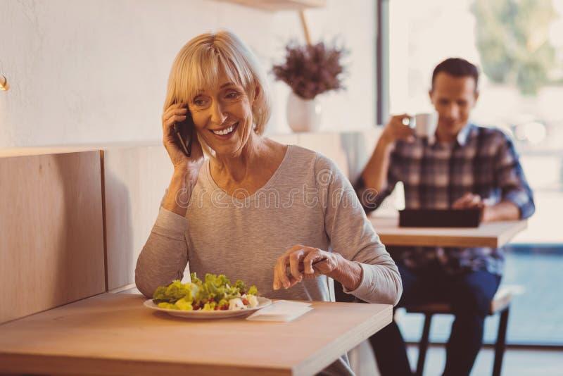 Mujer alegre que come la ensalada y que charla en el teléfono fotos de archivo libres de regalías