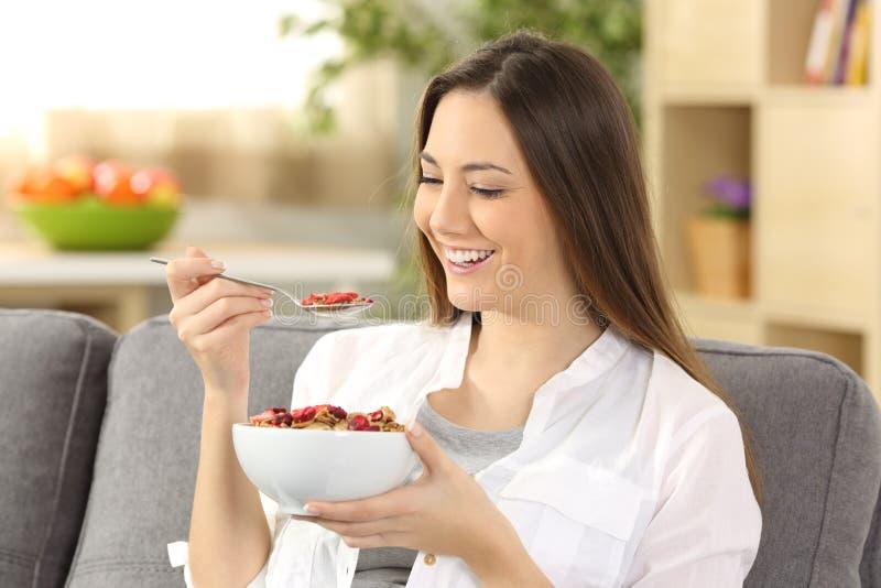Mujer alegre que come los cereales en casa foto de archivo