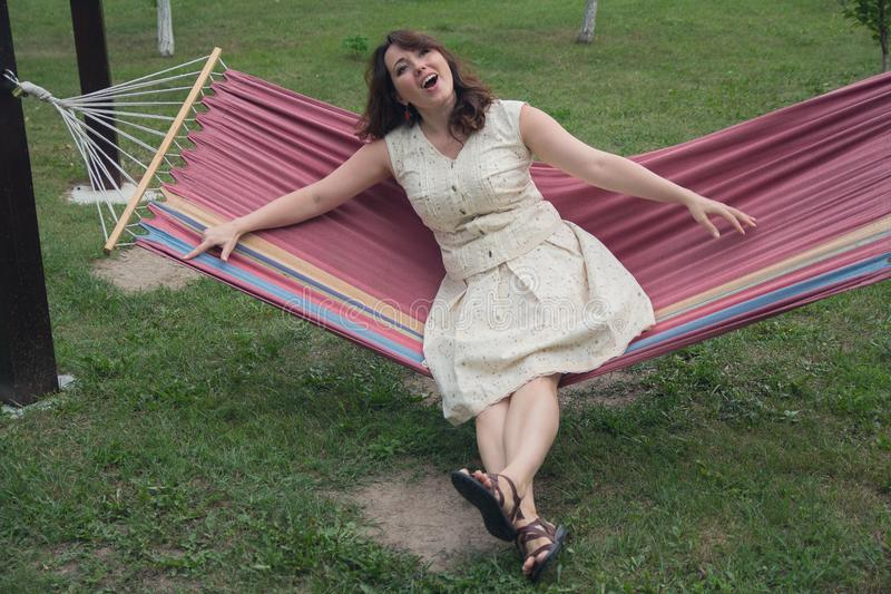 Mujer alegre que descansa en una hamaca fotos de archivo