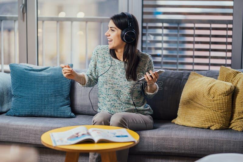 Mujer alegre que escucha la música con los auriculares grandes y que canta Disfrutando de escuchar la música en tiempo libre en c imagen de archivo libre de regalías