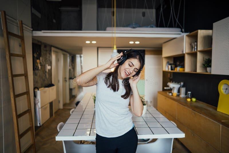 Mujer alegre que escucha la música con los auriculares grandes y que canta Terapia de música, práctica beneficiosa del humor Salu imagen de archivo libre de regalías