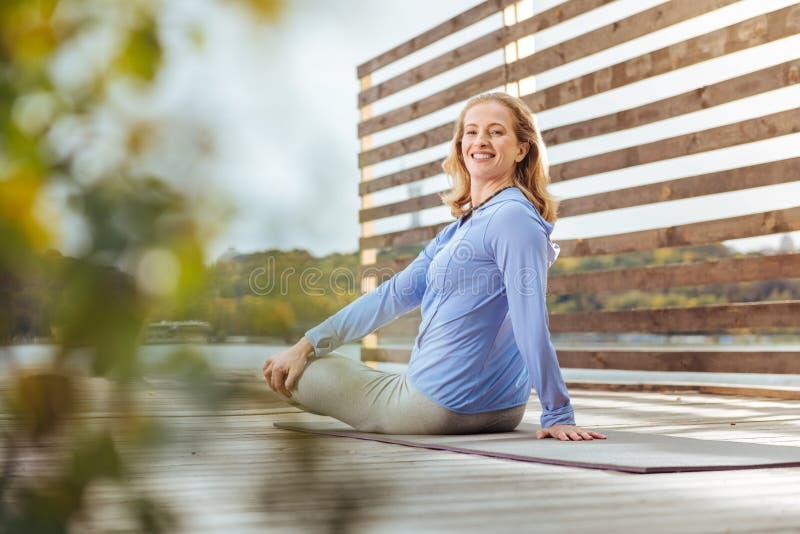 Mujer alegre que estira sus músculos traseros haciendo yoga imagen de archivo libre de regalías