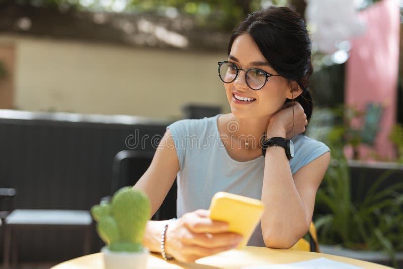 Mujer alegre que lleva los accesorios agradables que se sientan en terraza del verano fotos de archivo libres de regalías