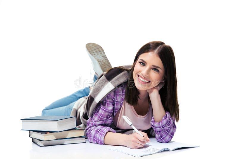 Mujer alegre que miente en el piso y que escribe en cuaderno imagenes de archivo