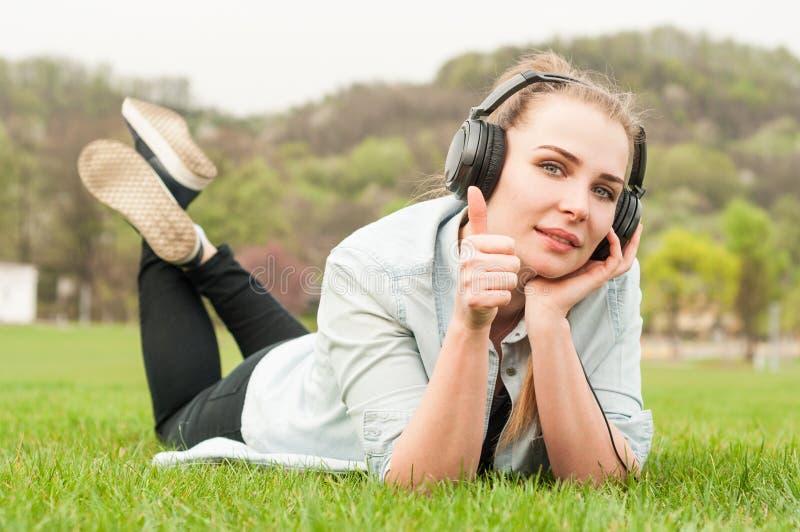 Mujer alegre que miente en hierba y que muestra los pulgares para arriba al aire libre foto de archivo libre de regalías