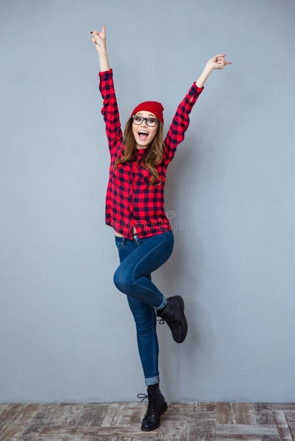 Mujer alegre que presenta con las manos aumentadas para arriba foto de archivo libre de regalías