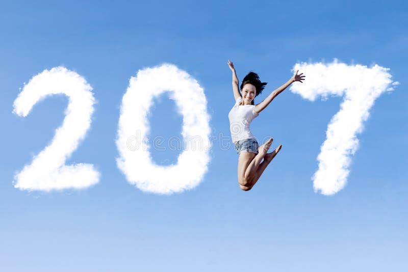 Mujer alegre que salta con 2017 imagen de archivo