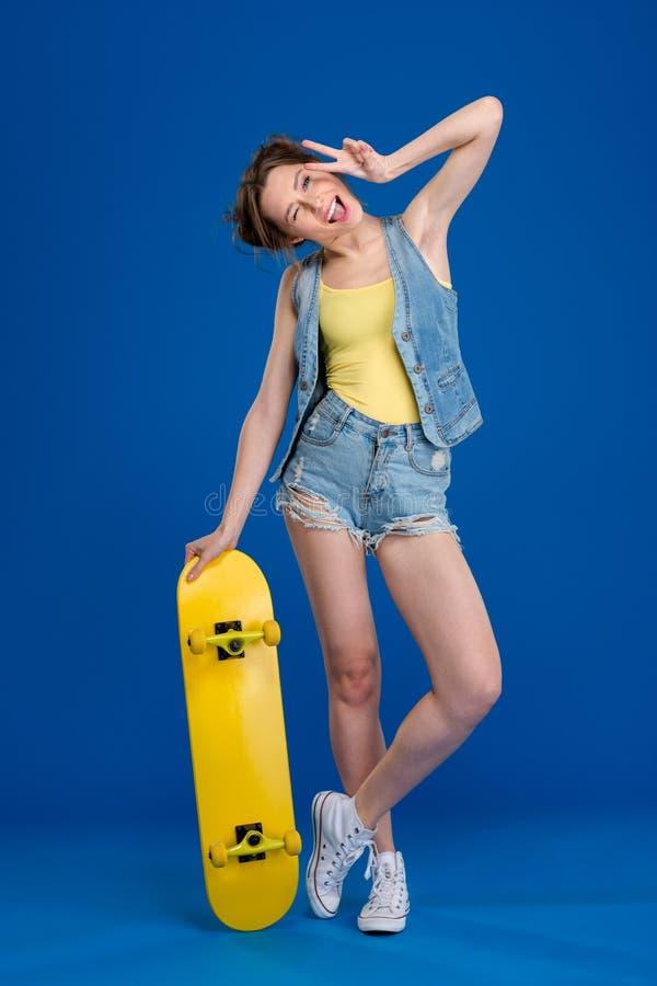 Mujer alegre que se coloca con el monopatín foto de archivo
