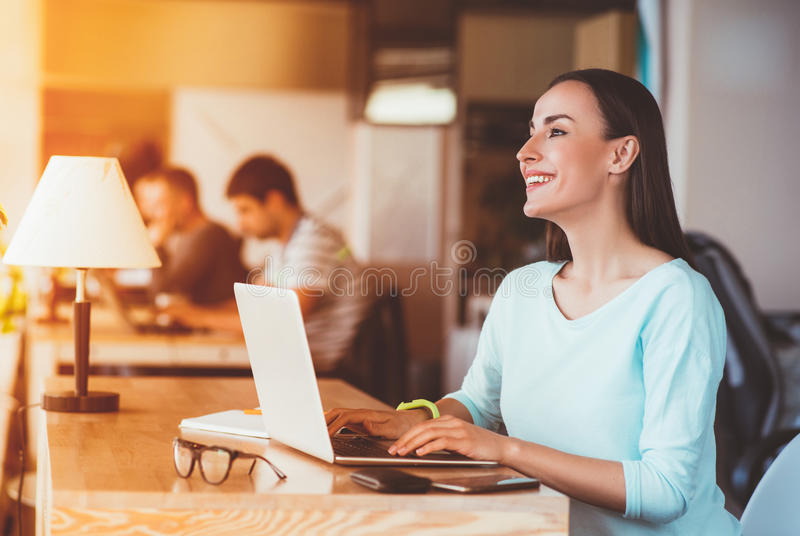 Mujer alegre que se sienta en la tabla fotos de archivo