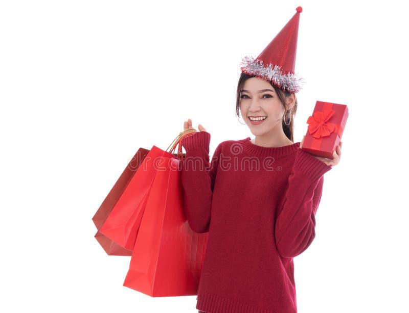 Mujer alegre que sostiene isola de la caja de regalo de la Navidad y del bolso de compras imagen de archivo
