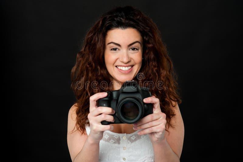 Mujer alegre que sostiene la cámara nuevamente lanzada fotografía de archivo libre de regalías