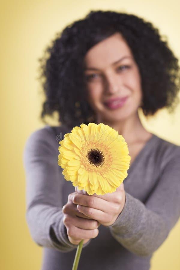 Mujer alegre que sostiene una flor amarilla fotografía de archivo