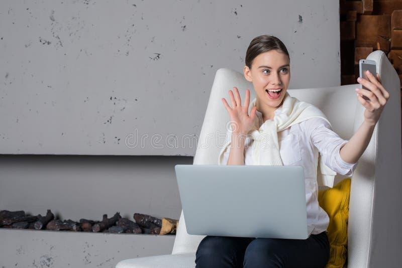 Mujer alegre que tiene llamada video con los amigos vía el teléfono móvil fotografía de archivo