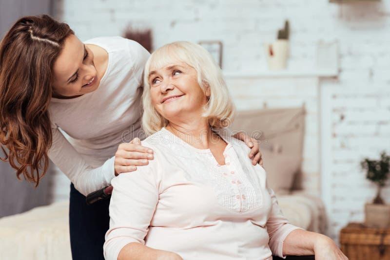 Mujer alegre que toma cuidado de su abuela en silla de ruedas foto de archivo
