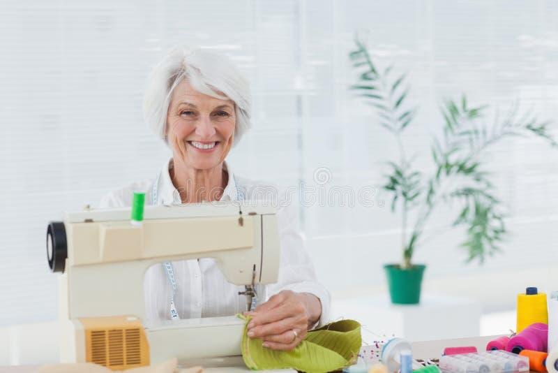 Mujer alegre que usa la máquina de coser en casa foto de archivo libre de regalías