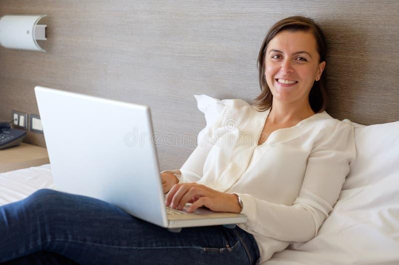 Mujer alegre que usa su ordenador portátil en la cama fotografía de archivo libre de regalías