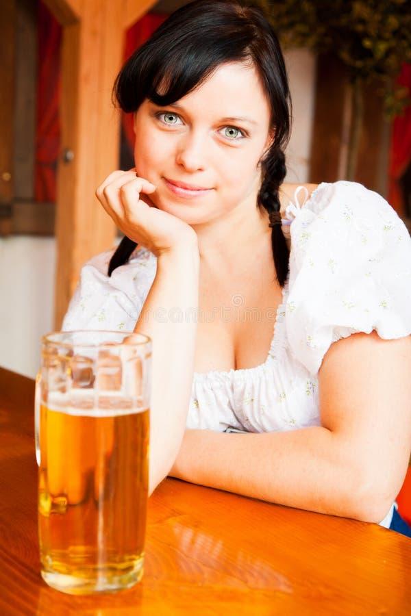 Mujer alemana joven que goza de una taza de cerveza fotografía de archivo libre de regalías