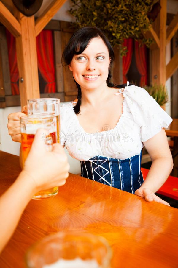 Mujer alemana joven que goza de una taza de cerveza imagen de archivo