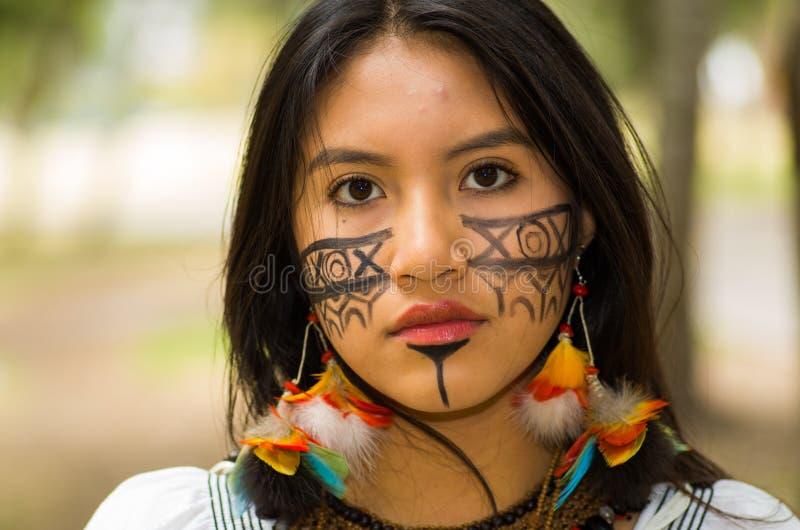 Mujer amazónica hermosa del Headshot, pintura facial indígena y pendientes con las plumas coloridas, presentando seriamente para foto de archivo libre de regalías