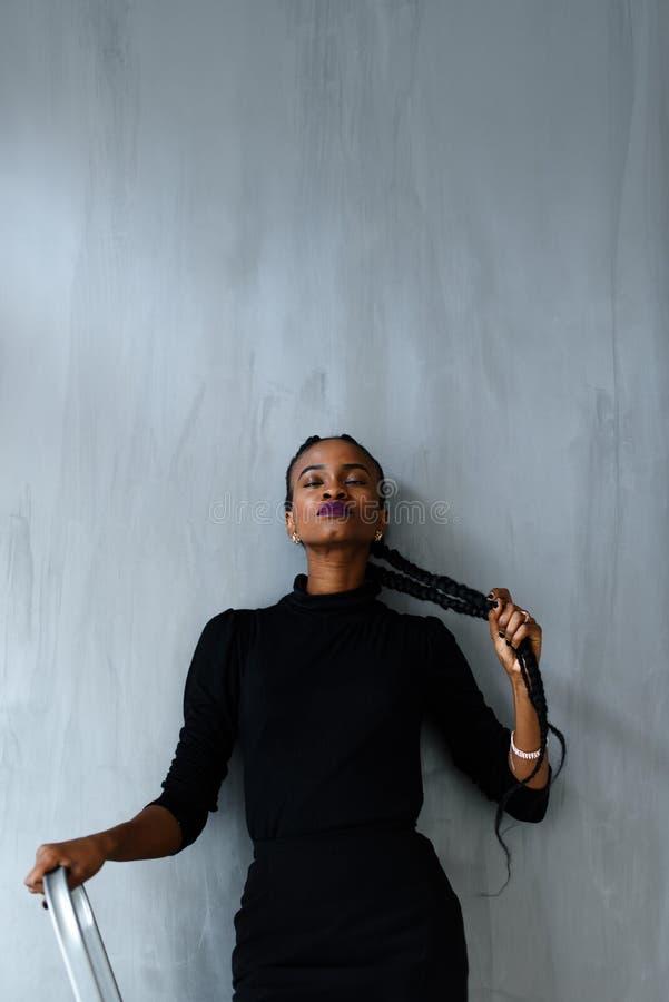Mujer americana bastante negra de los jóvenes que toca su trenza gruesa en fondo oscuro del estudio imagen de archivo