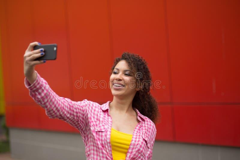 Mujer americana joven que toma el cuadrado del selfie a tiempo fotografía de archivo