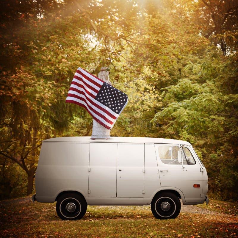 Mujer americana orgullosa que sostiene la bandera en el vintage Van imagen de archivo libre de regalías