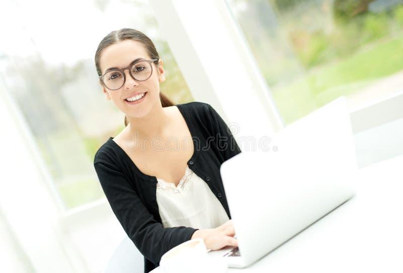 Mujer amistosa en lentes usando un ordenador portátil imagenes de archivo