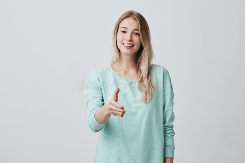 Mujer amistosa europea hermosa con el pelo largo rubio que lleva el suéter azul casual que sonríe ampliamente demostrándola imagenes de archivo