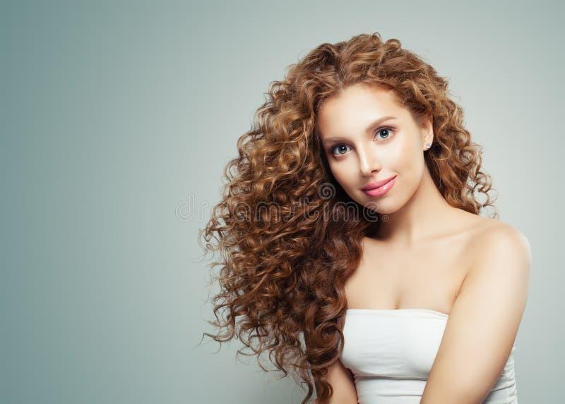 Mujer amistosa joven con el pelo ondulado sano largo en fondo gris imagen de archivo libre de regalías