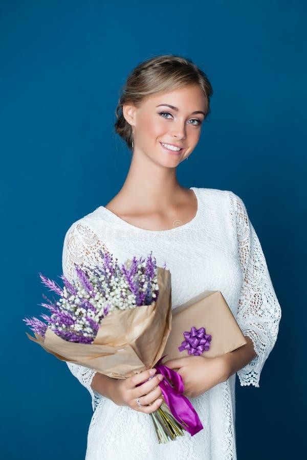 Mujer amistosa joven que sonríe y que sostiene el regalo imágenes de archivo libres de regalías