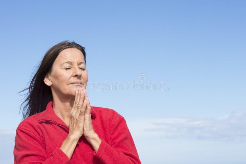 Mujer amistosa madura que medita y que ruega fotos de archivo libres de regalías