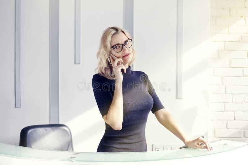 Mujer amistosa rubia hermosa detrás del mostrador de recepción, administrador que habla por el teléfono Sol en oficina moderna fotos de archivo libres de regalías