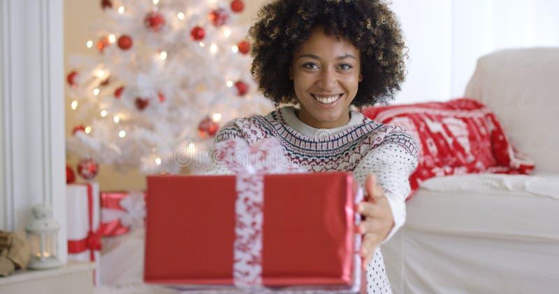 Mujer amistosa sonriente que ofrece un regalo de la Navidad fotografía de archivo