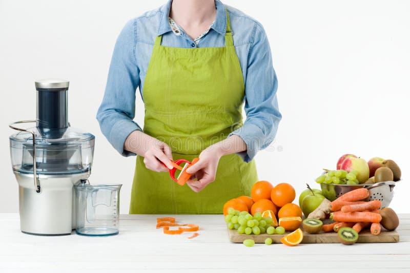 Mujer anónima que lleva un delantal, preparando el zumo de fruta fresca usando el juicer eléctrico moderno, concepto sano de la f imagen de archivo libre de regalías