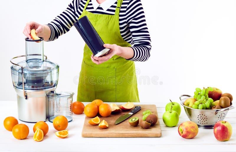 Mujer anónima que prepara el zumo de fruta fresca usando el juicer eléctrico, concepto sano del detox de la forma de vida en el f imagenes de archivo