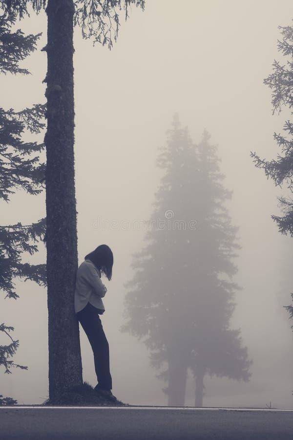 Mujer anónima que se inclina contra árbol foto de archivo libre de regalías