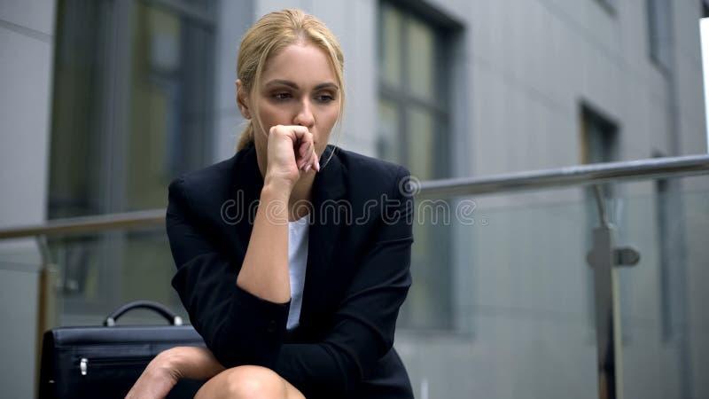Mujer ansiosa que se sienta en el banco, preocupante sobre despido del trabajo, depresión imagenes de archivo